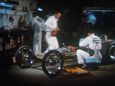 vídeos de stock, filmes e b-roll de 1959 medium shot mechanics working on race car in auto shop - hot rod
