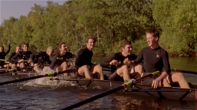 medium shot members of crew team celebrating win in racing shell on charles river - scull stock videos & royalty-free footage