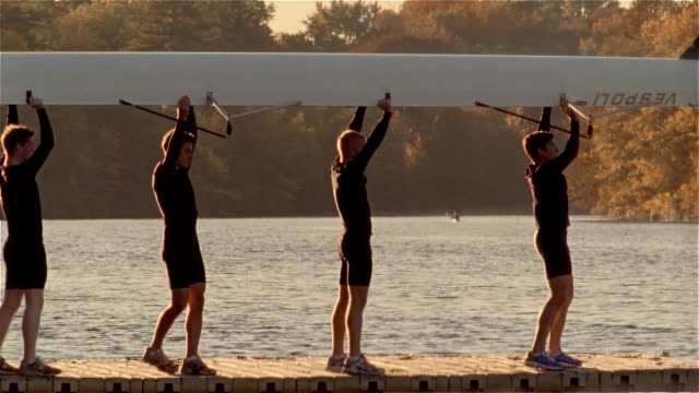 medium shot members of crew team standing on dock and placing racing shell in water - canottaggio video stock e b–roll