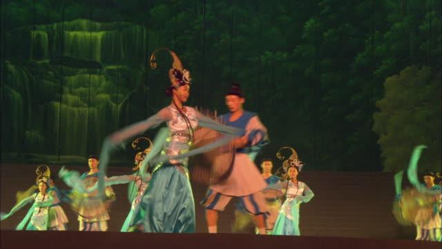 Medium shot men and woman dancing in elaborate costumes at Confucius theatre / Qufu