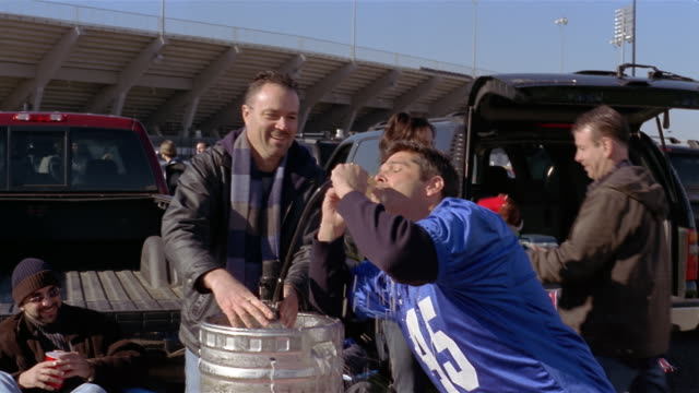 medium shot men and women at tailgate party/ man drinking squirting beer from keg/ connecticut - drinking beer stock videos and b-roll footage