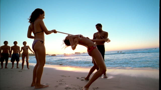 medium shot men and women doing limbo on beach - 数人点の映像素材/bロール