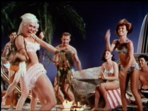 1963 medium shot men and women in bikinis dancing in beach party scene on film set - bikini stock-videos und b-roll-filmmaterial