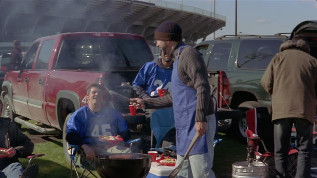 medium shot men at tailgate party laughing as they refuse burnt hot dogs and hamburgers from grill/ connecticut - cool box stock videos & royalty-free footage
