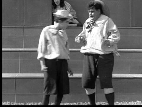 1918 b/w medium shot men dressed as boys arguing and fighting as woman dressed as girl watches from step - oliver hardy stock videos & royalty-free footage