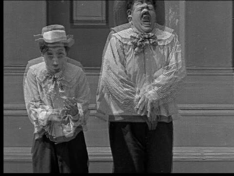 1918 b/w medium shot men (left: billy west, right: oliver hardy) dressed as boys/ boy offering crying friend something from his pocket/ large crying boy suddenly getting happy/ boys falling back on steps - oliver hardy stock videos & royalty-free footage