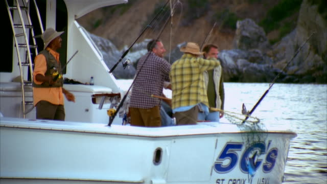 stockvideo's en b-roll-footage met medium shot men fishing from back of boat/ zoom out men on boat/ long beach, california - noordelijke grote oceaan