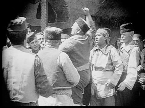 1916 b/w medium shot men in town square debating passionately/ man pulling speaking man off of chair/ man sitting down - menschliche gliedmaßen stock-videos und b-roll-filmmaterial