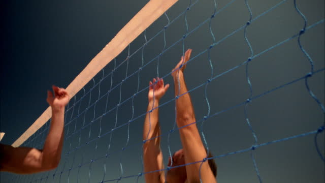 Medium shot men jumping for ball at net / player blocking ball