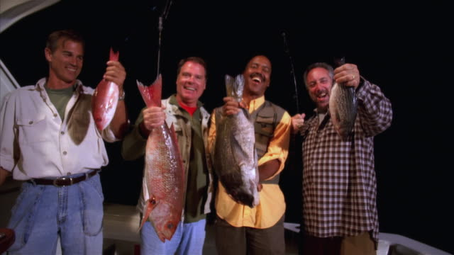 Medium shot men on fishing boat holding up fish and smiling/ Long Beach, California