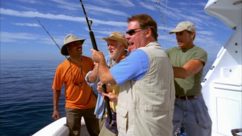 medium shot men on stern of boat surrounding friend with fish on line as he struggles/ california - male friendship stock videos & royalty-free footage