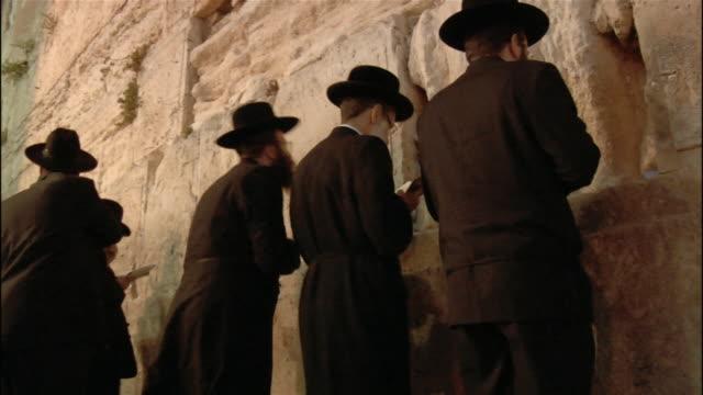 medium shot men praying at wailing wall/ jerusalem - wailing wall stock videos & royalty-free footage