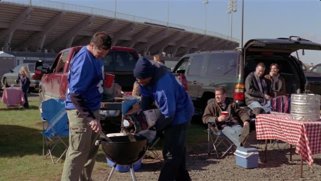 medium shot men setting up barbeque grill at tailgate party/ connecticut - アメフトのユニフォーム点の映像素材/bロール
