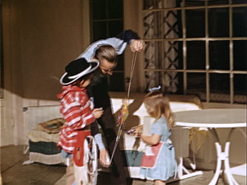 1940 medium shot men showing toy to young girl wearing dress and boy wearing cowboy costume on patio / los angeles, california, usa  - 1940 stock-videos und b-roll-filmmaterial