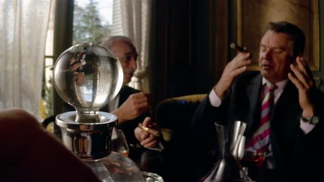 Medium shot men smoking cigars and talking / dolly shot decanter + flask of brandy on table / man lighting cigar in foreground