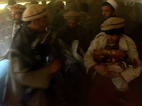 medium shot men sneaking in and grabbing blankets from tent where us military is handing them out - aggression stock-videos und b-roll-filmmaterial