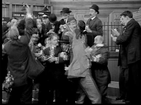1909 b/w medium shot men trading furiously at commodities exchange/  businessman stepping in and taking control - 1900 1909 stock-videos und b-roll-filmmaterial