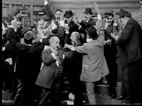 1909 b/w medium shot men trading furiously at commodities exchange/  businessman stepping in and taking control - chaos stock videos & royalty-free footage