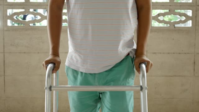medium shot : men walk with walking frame - disability stock videos and b-roll footage