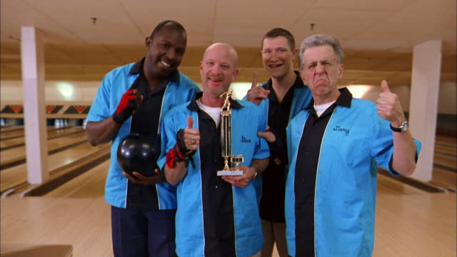 vídeos de stock e filmes b-roll de medium shot men's bowling team in blue jerseys holding trophy and smiling at cam - 55 59 anos