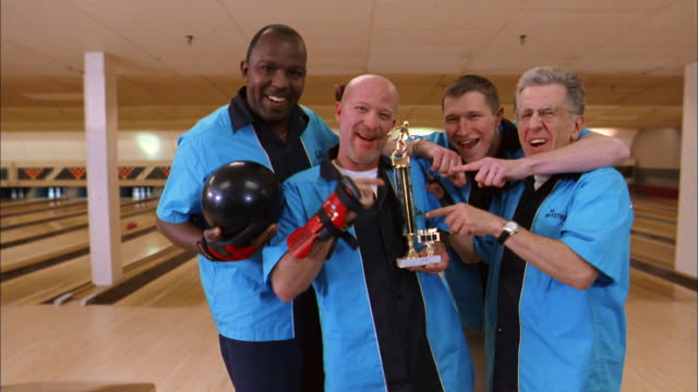 vídeos de stock e filmes b-roll de medium shot men's bowling team in blue jerseys holding trophy / smiling and gesturing at cam - equipamento de equipa