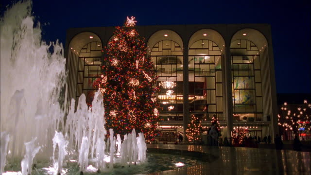Medium shot Metropolitan Opera House fountain and Christmas tree at night / NYC