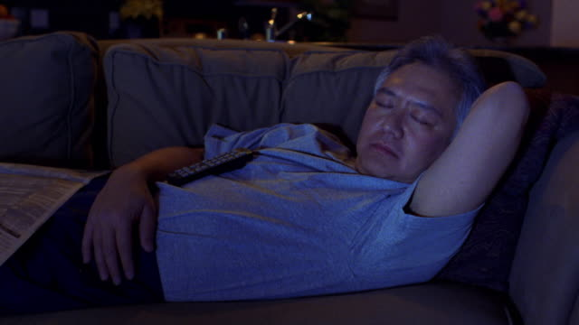 medium shot middle age asian man sleeping on couch with television remote on stomach - mature adult stock videos & royalty-free footage