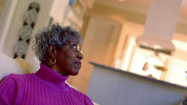 vídeos y material grabado en eventos de stock de medium shot middle age black woman reaching for telephone as man talks & paces with coffee mug in living room - teléfono sin cable