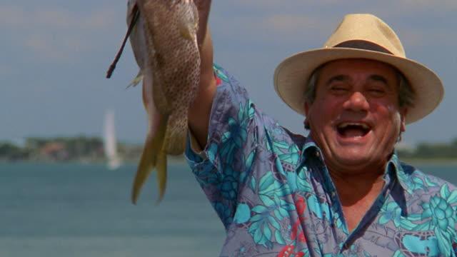 Medium shot middle aged man holding up line of fish / kissing fish