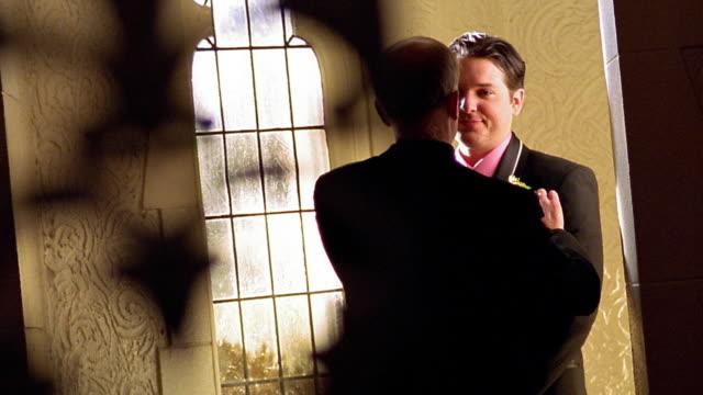 Medium shot middle aged man talking to groom / adjusting groom's coursage
