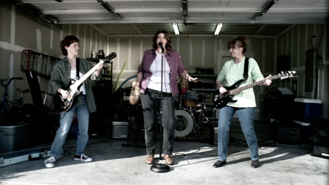 medium shot middle aged women performing in garage band - rock group stock videos & royalty-free footage