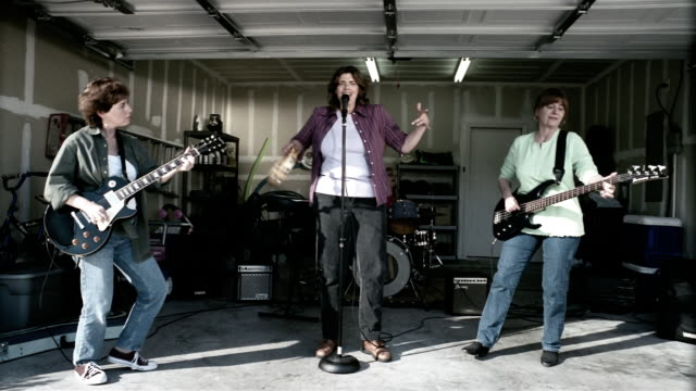 Medium shot middle aged women performing in garage band