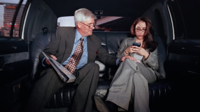 Medium shot middle-aged businessman looking at binder and young businesswoman using pda /man repeatedly putting his hand on woman's knee in limo / woman removing his hand