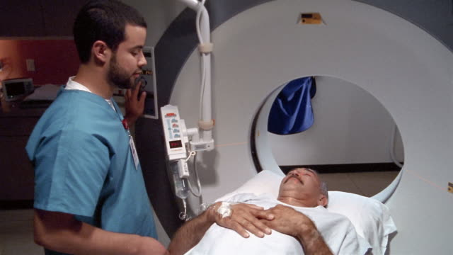 medium shot middle-aged patient getting head ct in ct scan machine operated by technologist / el paso, texas - radiologist stock videos & royalty-free footage