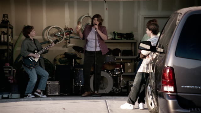 medium shot middle-aged women performing in garage rock band / teenage girls dancing / forcing teenage boy by the arm to join them - performance group stock videos and b-roll footage