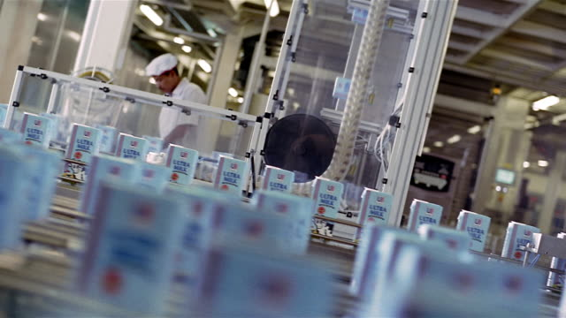 medium shot milk cartons moving on conveyor belts and technicians working in background at ultra jaya plant / indonesia - food processing plant stock videos and b-roll footage