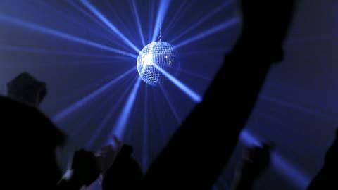 medium shot mirror ball spinning and reflecting blue light rays with arms of dancers raised in nightclub - nattklubb bildbanksvideor och videomaterial från bakom kulisserna