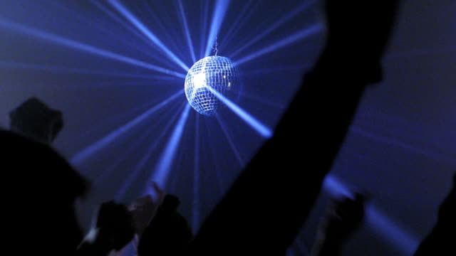 Medium shot mirror ball spinning and reflecting blue light rays with arms of dancers raised in nightclub