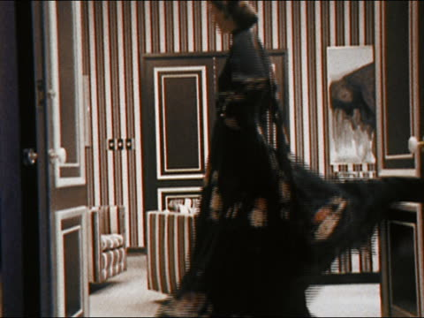 vídeos de stock e filmes b-roll de 1971 medium shot model twirling around wearing long dress in room with striped wallpaper and furniture - papel de parede