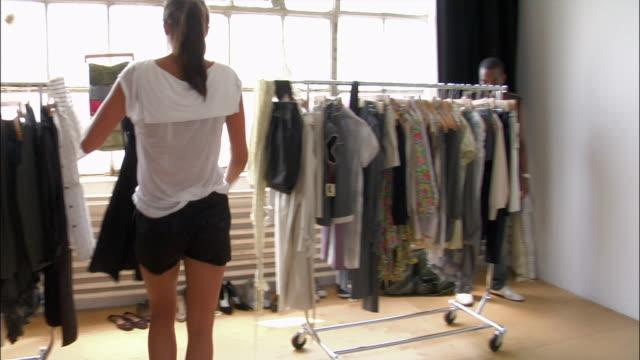 Medium shot model walking to clothing racks / panning to other women in atelier