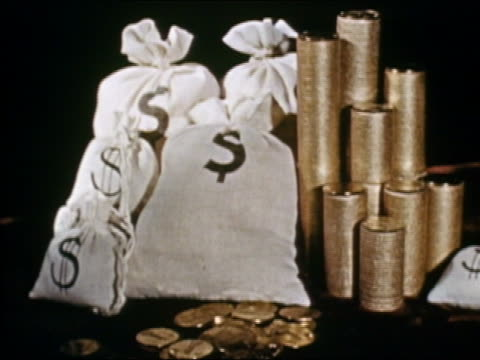 1941 medium shot money bags and stacks of gold coins / hand throwing coins on pile / AUDIO