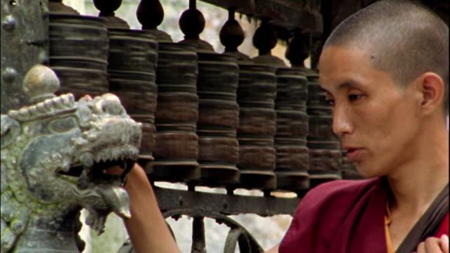 Medium shot monk spinning prayer wheels at Swayambhunath Temple / Kathmandu, Nepal