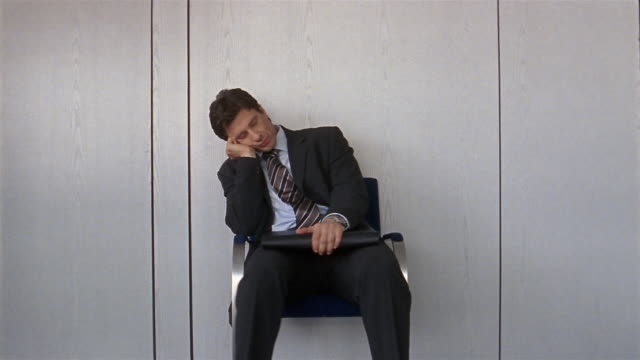 vidéos et rushes de medium shot montage of anxious businessman waiting outside office - chaise