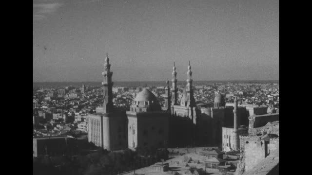 stockvideo's en b-roll-footage met medium shot mosque and city and waterfront in bkgd / city skyline and waterfront / closer shots mosque minarets / mosque dome with geometric pattern... - caïro