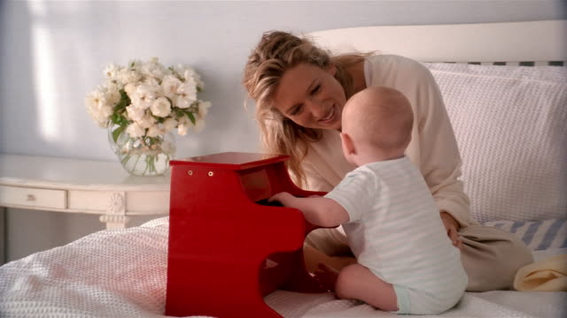 medium shot mother and baby playing toy piano on top of bed - babygro stock videos & royalty-free footage