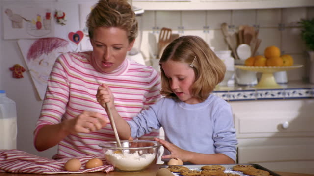 medium shot mother and daughter baking cookies / daughter cracking eggs into bowl of flour - chocolate chip cookie stock videos and b-roll footage