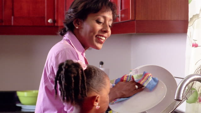 vidéos et rushes de medium shot mother and daughter doing dishes / mother kissing daughter on cheek - sécher activité