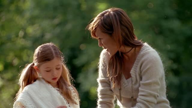 vidéos et rushes de medium shot mother and daughter sitting outside talking - contrarié