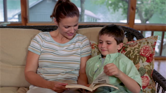 medium shot mother and son reading book on sofa in lakehouse / view of lake through windows - clarkesville stock videos & royalty-free footage