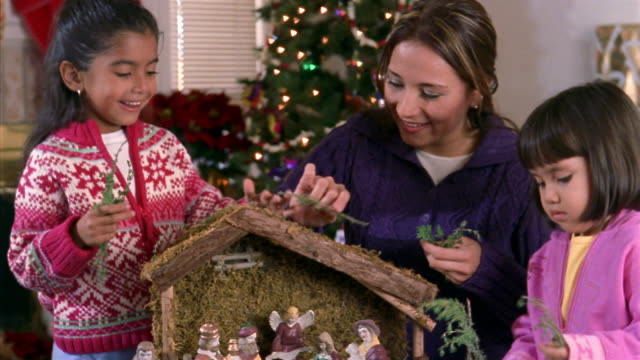 medium shot mother and two young daughters setting up nativity scene / christmas tree in background - キリスト降誕点の映像素材/bロール